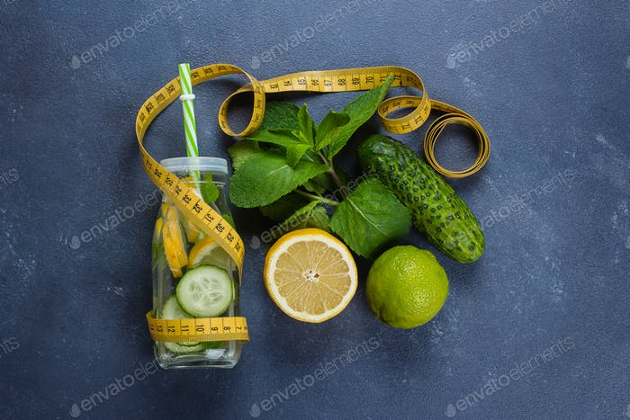 Cold detox water with lemon, cucumber, mint in glass bottle. Organic healthy water for weight loss