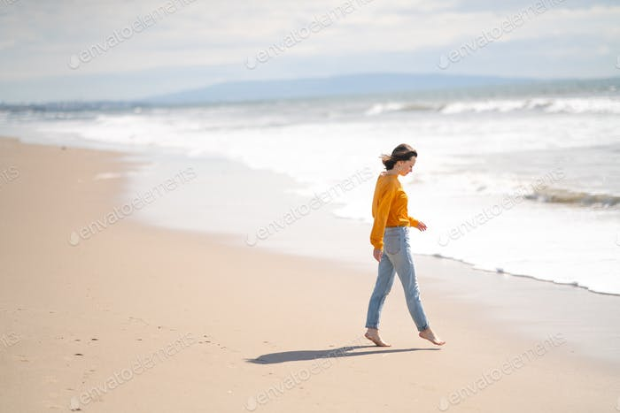 Young barefoot girl on the beach
