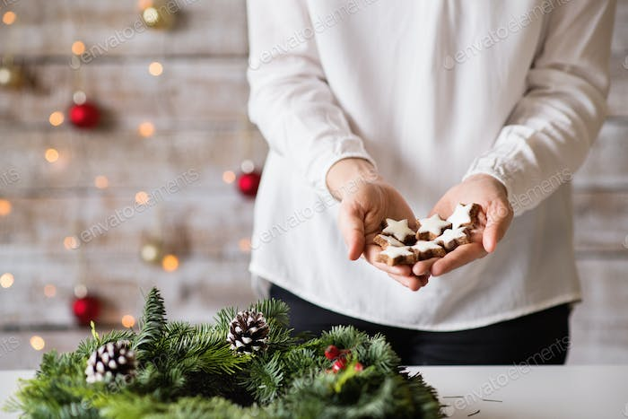 Young woman holding star shaped Christmas cookies.