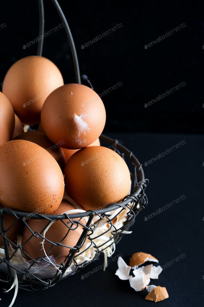 Basket with close up fresh farm natural chicken eggs on a black background. Farm eco friendly