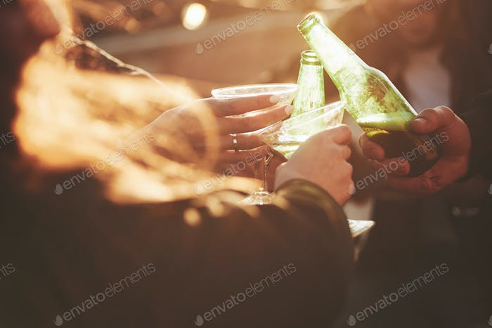 Knocking glasses and bottles. It's rooftop party. Group of friends have holidays at sunny autumn day
