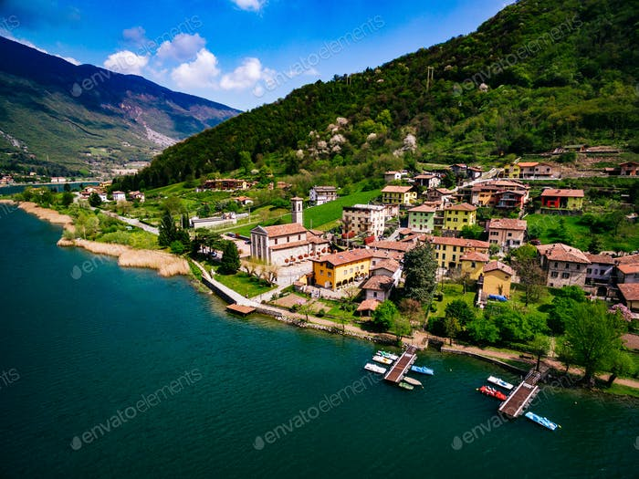 Aerial view of beautiful spring landscape with Italian village by turquoise lake Endine, Italy