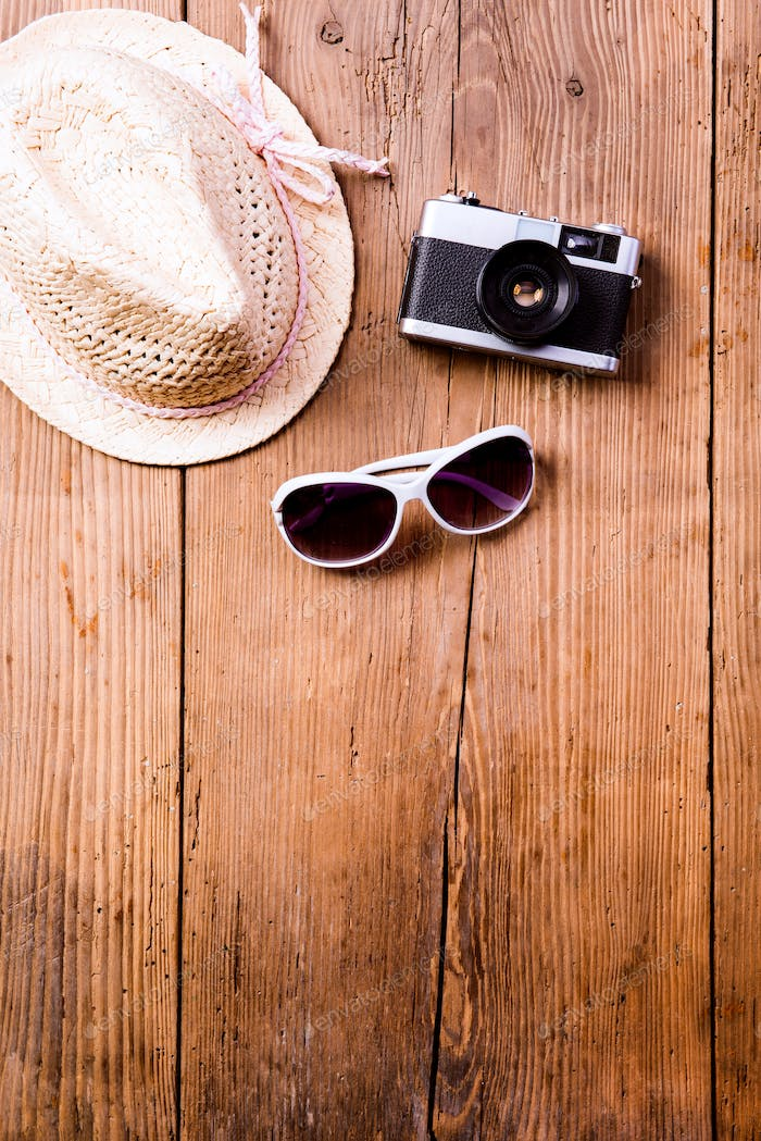 Sunglasses, hat and vintage camera against wooden background.