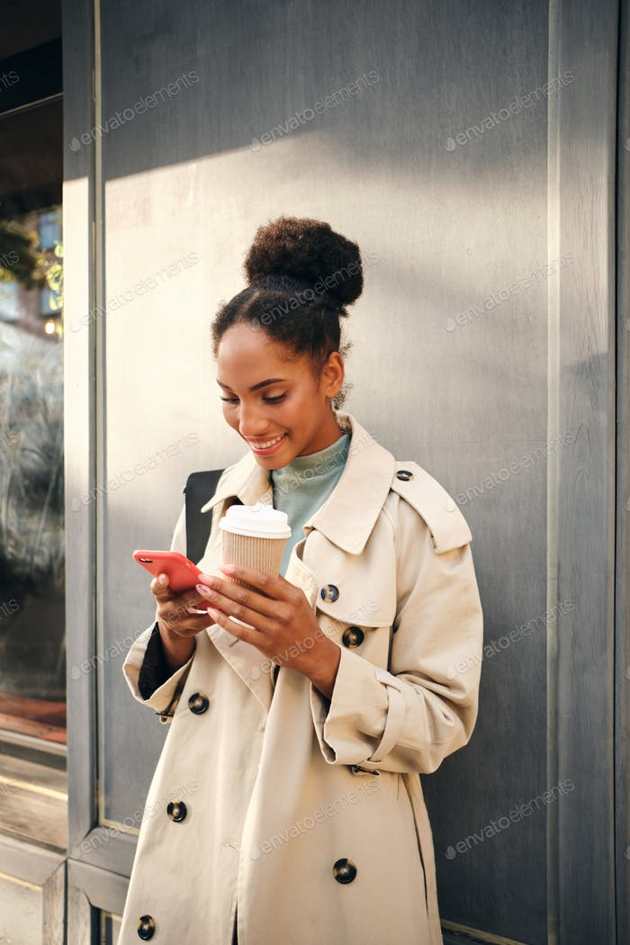 Beautiful African American girl in stylish trench coat with coffee joyfully using cellphone outdoor