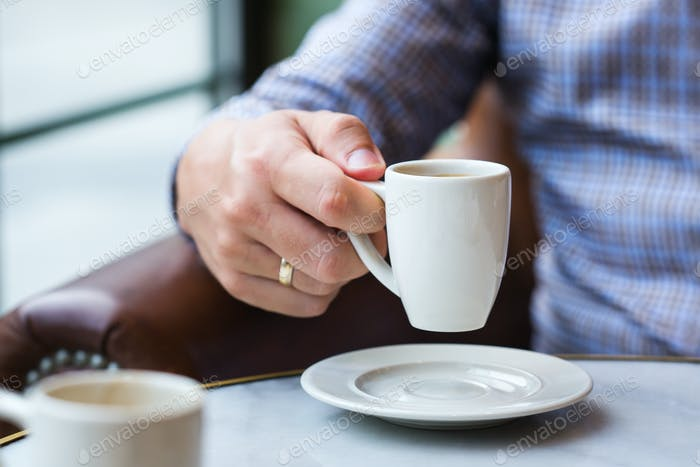 Businessman sitting in a cafe and drinking morning coffee