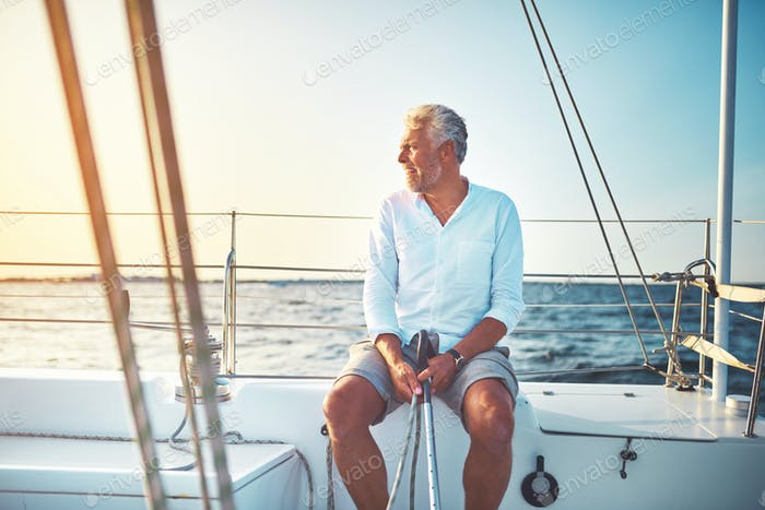 Mature man sitting on the deck of his sailboat