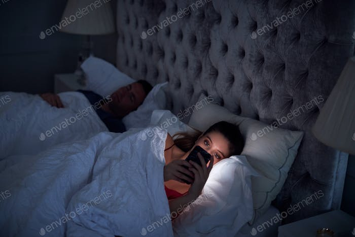 Woman Lying In Bed Checking Mobile Phone Whilst Man Sleeps Next To Her