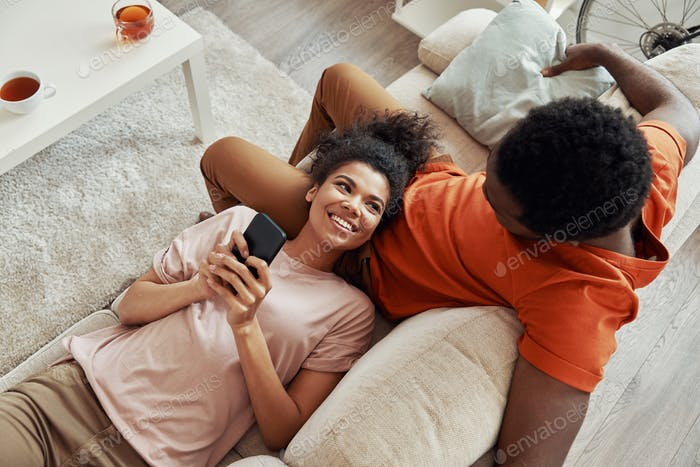 Top view of young African woman using smart phone and smiling