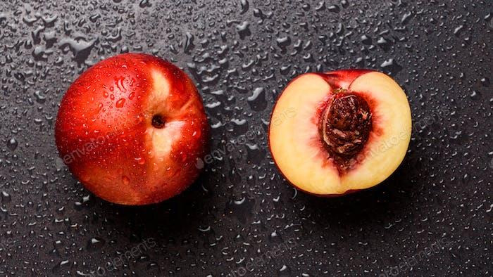 Nectarine fruit isolated on wet black background