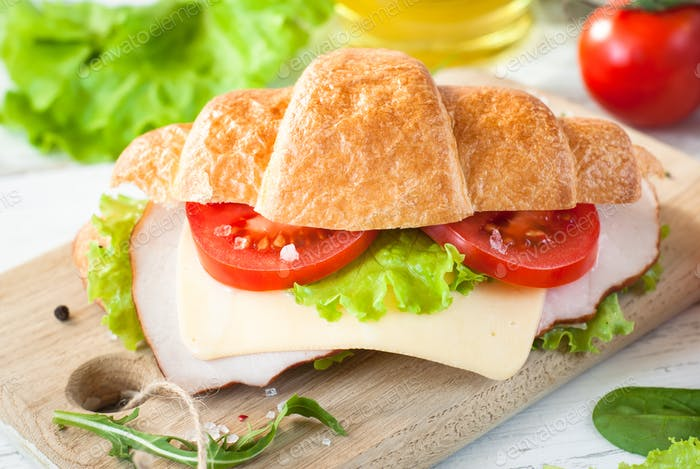 Croissant sandwich with bacon, cheese, lettuce and tomato