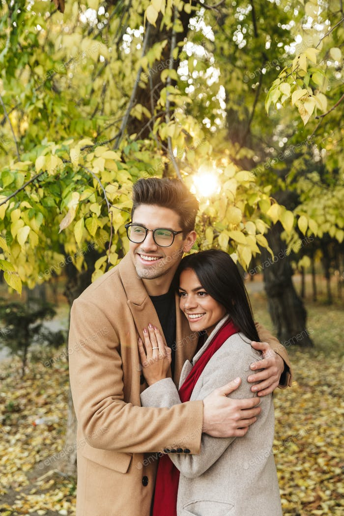 Portrait of nice charming couple smiling and hugging each other under tree in autumn park