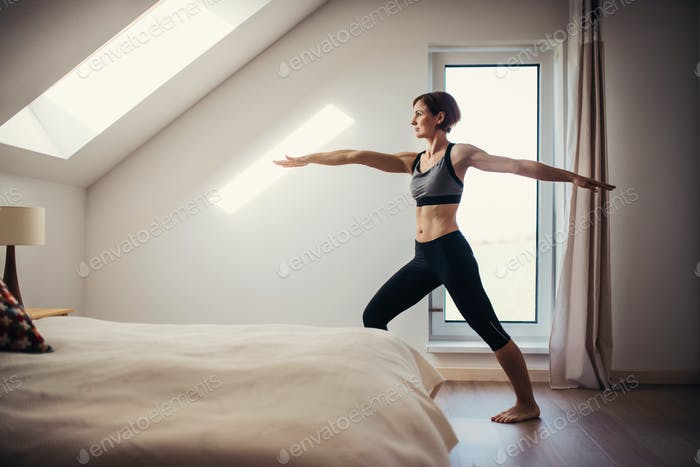 Side view of young woman doing exercise indoors in a bedroom. Copy space.