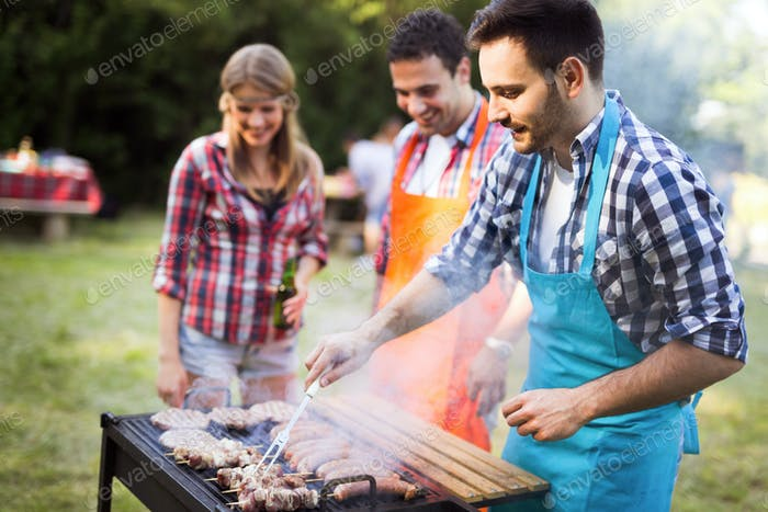 Happy young and joyful friends enjoying barbecue party