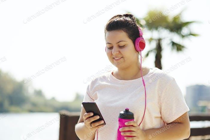 Woman choosing playlist for morning running