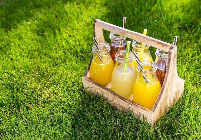 Sortiment von Limonade und Eistee in Flaschen in Holzregal im Gras