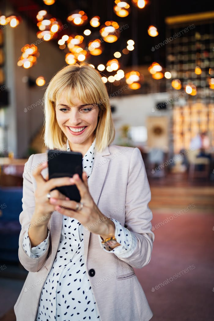 Beautiful business woman using smart phone and working