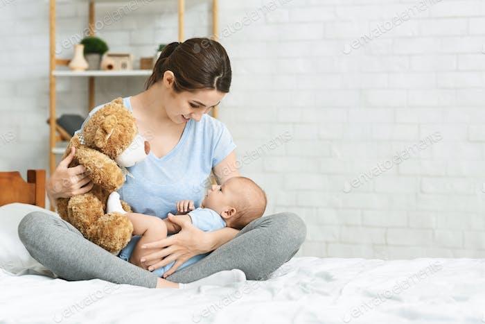 Junge Mutter hält Teddybär, spielt mit ihrem neugeborenen Baby