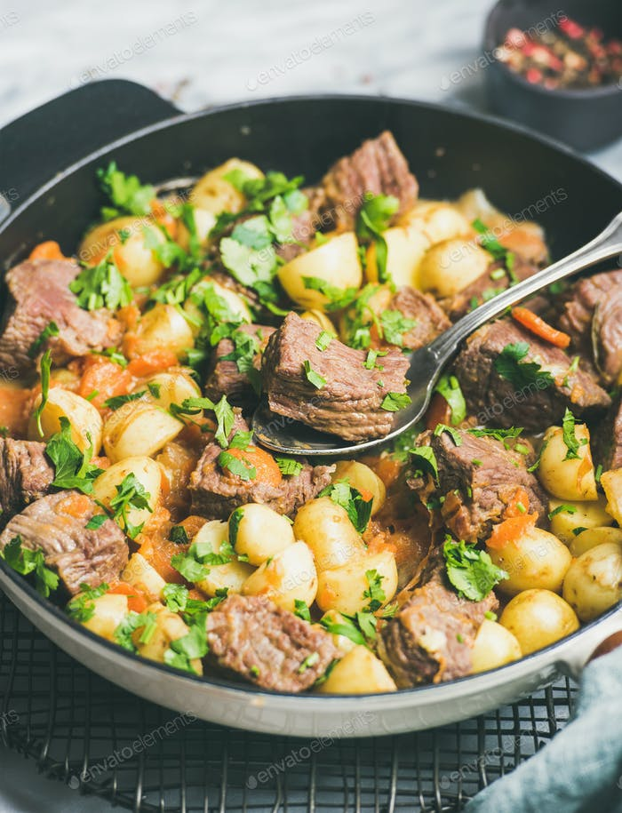 Braised beef meat with potato and carrot, vertical composition