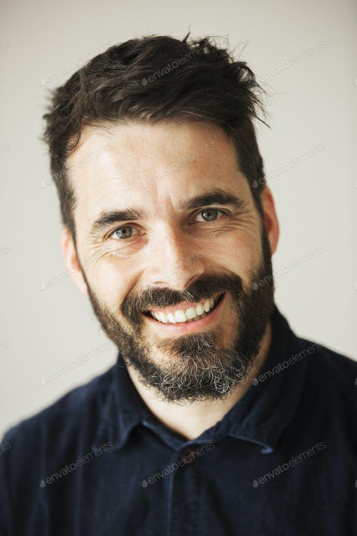 Портрет бородатого человека, улыбающегося на камеру.