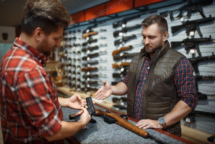 Мужчина с владельцем, выбирая пистолет в оружейном магазине