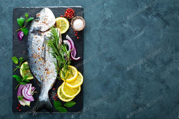 Fresh fish dorado. Raw dorado fish and ingredient for cooking on board. Sea bream