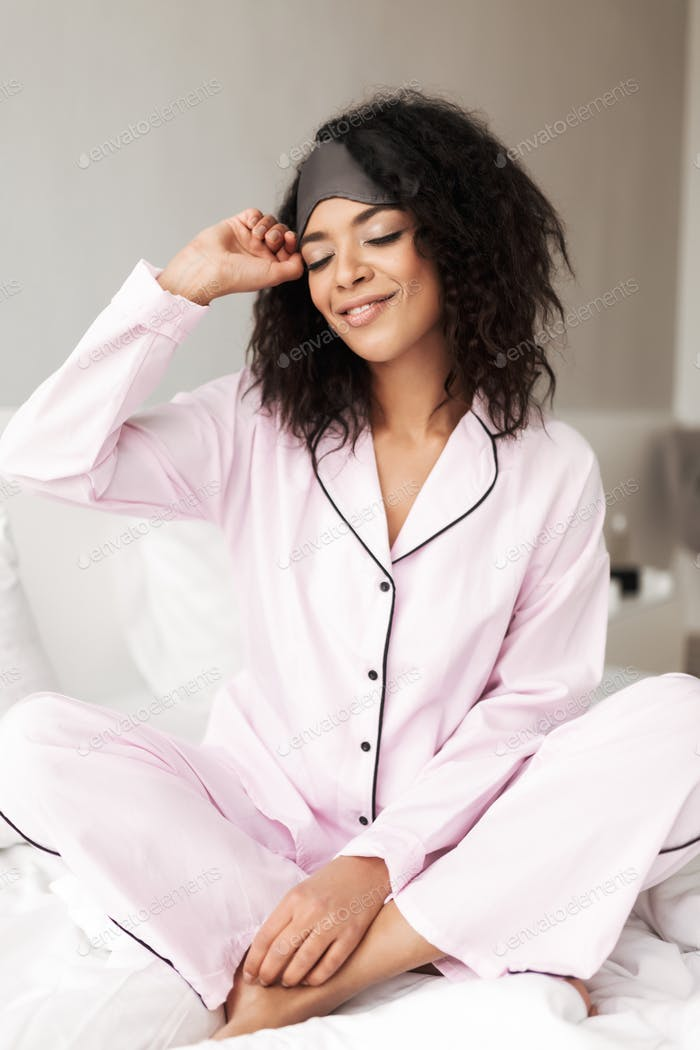 Beautiful woman with curly hair sitting on bed with eye mask on head and dreamily closing her eyes