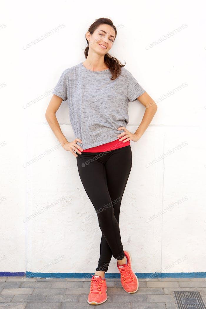 zuversichtlich junge Frau in Sportbekleidung stehen an einer weißen Wand