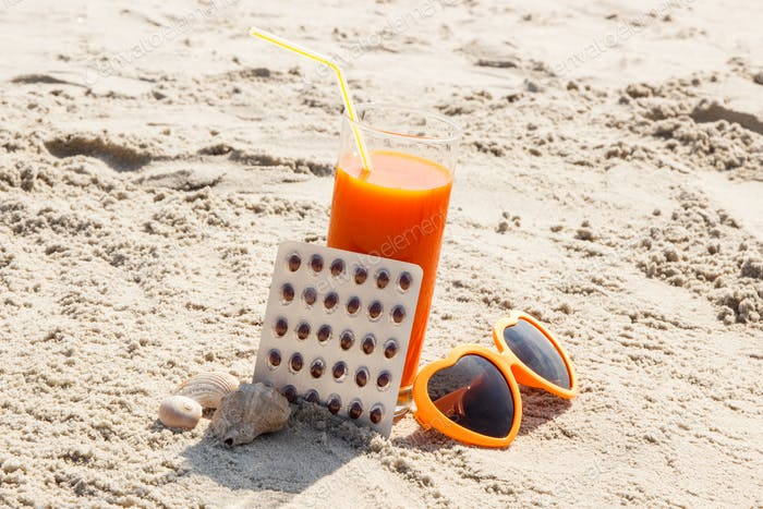 Medical pills, carrot juice and sunglasses on sand, vitamin A and beautiful, lasting tan