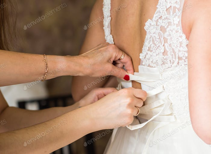 Bridesmaid is helping the bride to dress