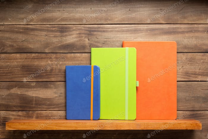 note book or notepad at shelf on wooden background