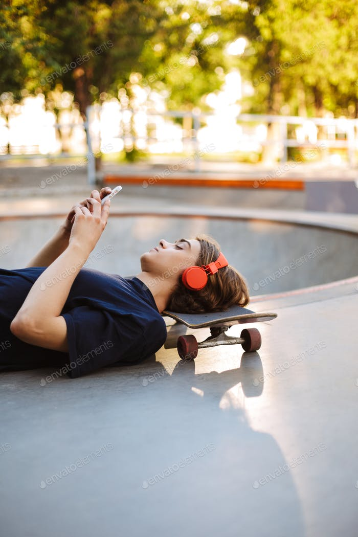 Young skater in orange headphones lying on skateboard while drea