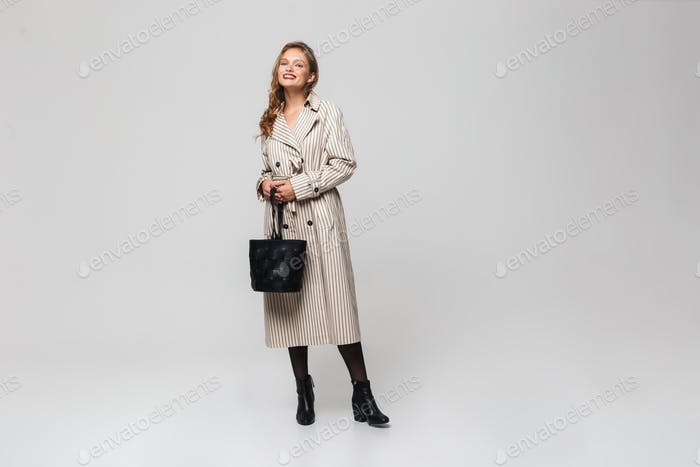 Attractive smiling woman in coat holding black bag in hands happily looking in camera. Full length