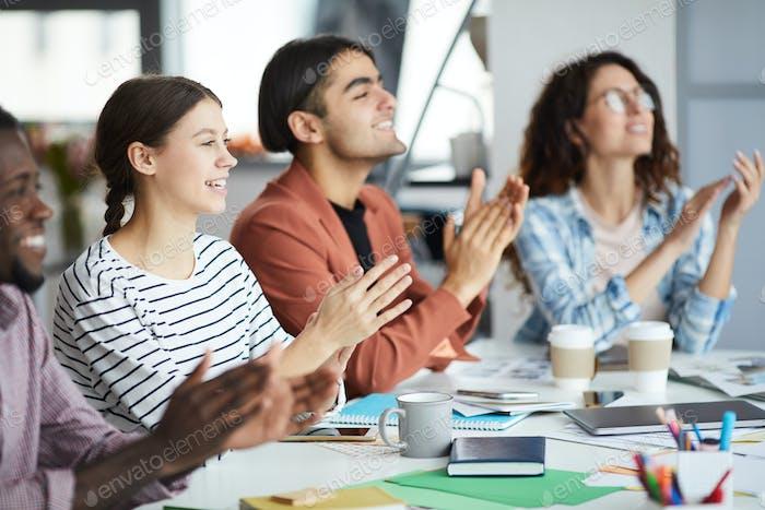 Reihe junger Geschäftsleute applaudieren