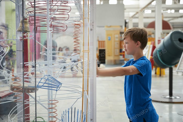 Young boy stands looking at a science exhibit, side view