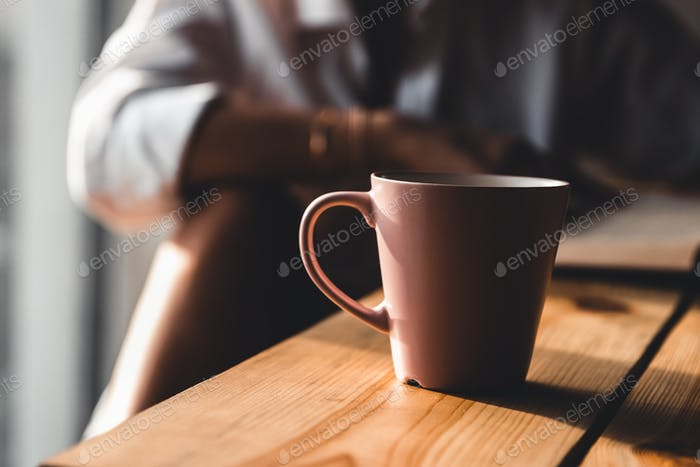Frau am Morgen trinkt Kaffee und liest altes Buch in einem weißen Hemd. Bildung, trinken. Maniküre