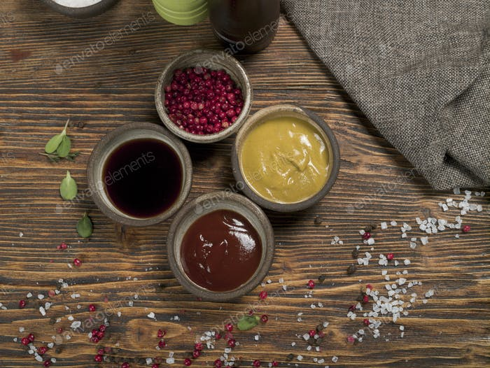 Different spices and sauces with a gray linen tablecloth on a wooden background, top view