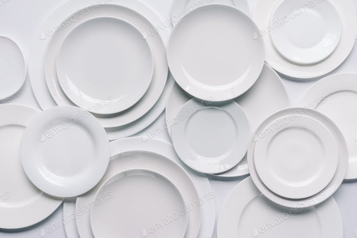 white plates composition on white background