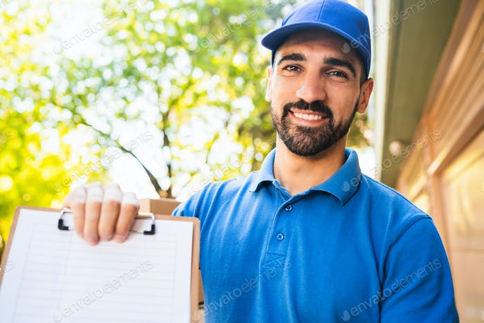 Delivery man giving the clipboard to a client to sign.
