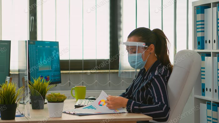 Woman with face mask checking reports