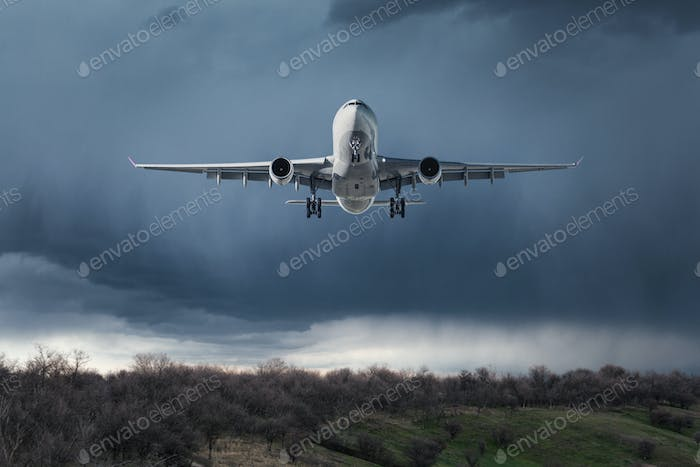 White passenger airplane is flying in the sky with clouds