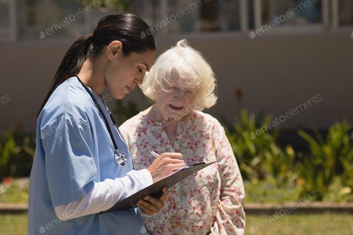 Seitenansicht der jungen Ärztin diskutieren medizinischen Bericht mit Senior Frau im Garten am sonnigen Tag