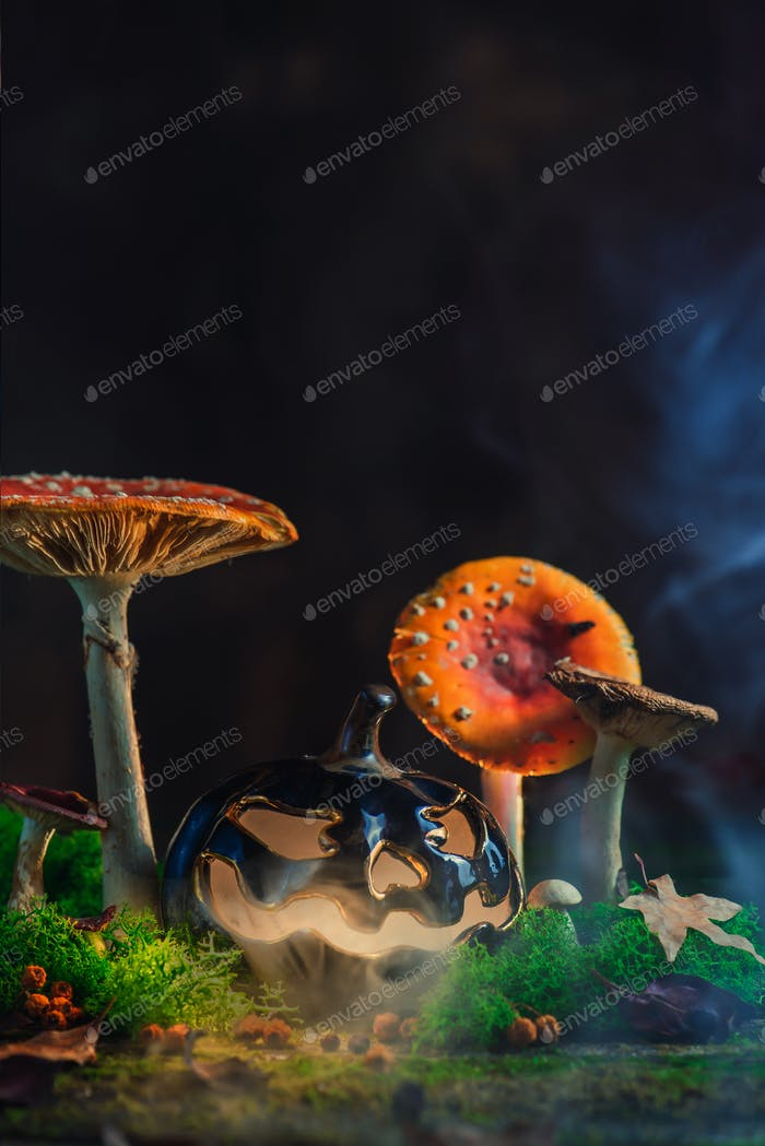 Spooky Halloween concept with a ceramic pumpkin among poisonous mushrooms. Creative autumn still