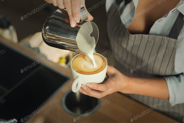 Closeup of barmen pouring milk to cappuccino cup