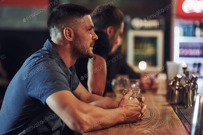 Вид сбоку. Друзья отдыхают в пабе с пивом в руках. Разговор