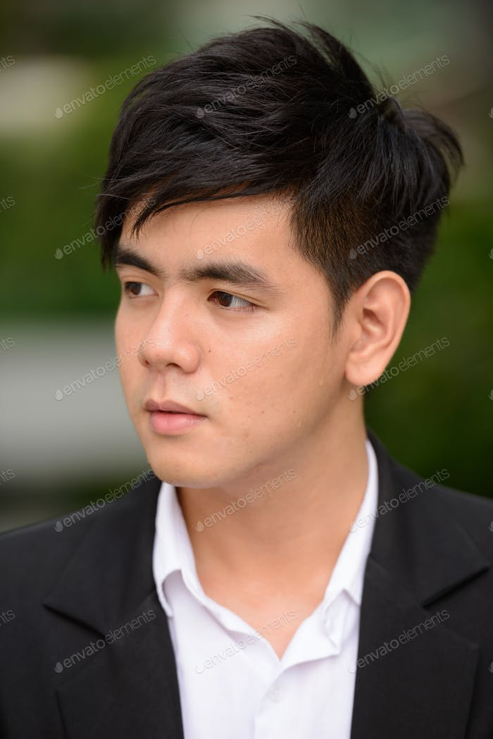 Face of young handsome Asian businessman thinking at the park