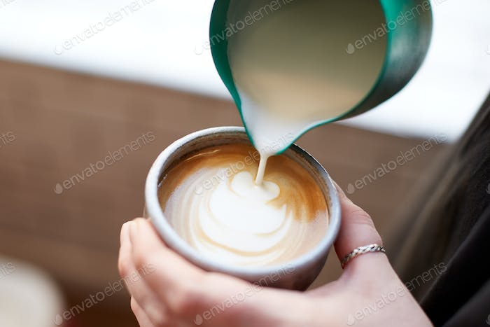 Close Up Of Barista Making Design In Cup Of Coffee At Cafe