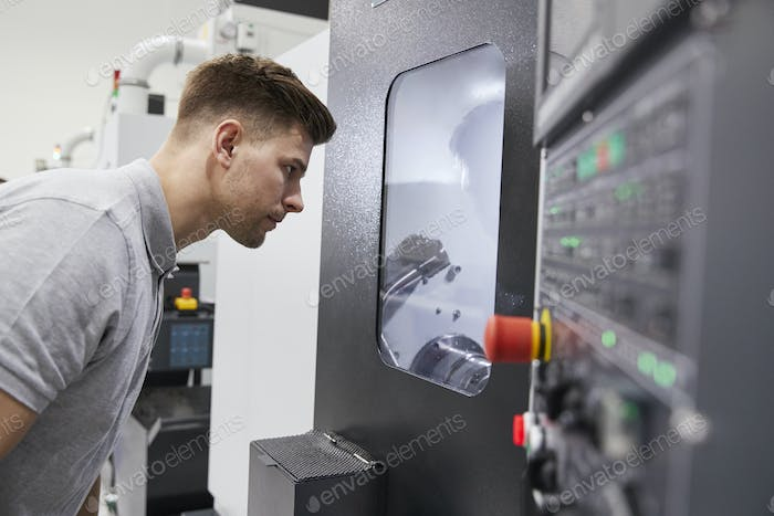 Male Engineer Watching Progress Of CNC Machinery In Factory