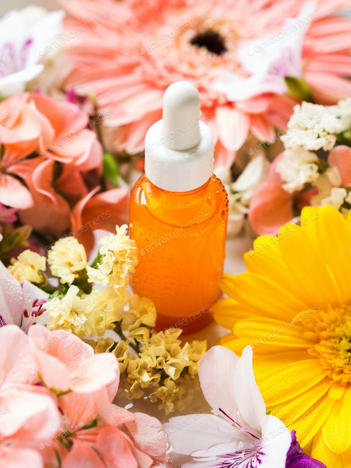 Skin care serum in orange bottle with flowers