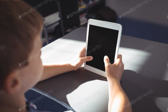 Boy using tablet computer at desk