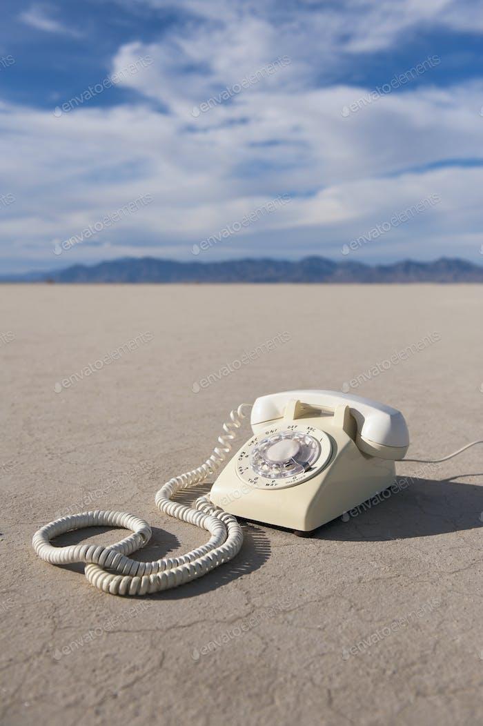 Vintage telephone on salt flat.